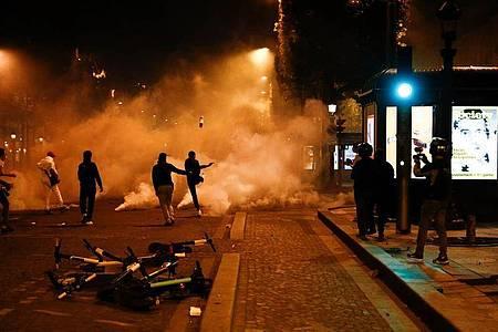 Fans von Paris Saint-Germain treten auf der Champs-Elysées gegen Tränengaskanister. Foto: Sameer Al-Doumy/AFP/dpa