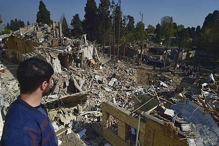 Ein Mann betrachtet die Überreste von Häusern, die durch armenischen Artilleriebeschuss zerstört wurden. Foto: Uncredited/AP/dpa