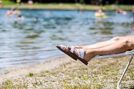 Eine Frau liegt bei sommerlichen Temperaturen an einem Badesee. Foto: Thomas Warnack/dpa/Symbolbild