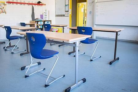Stühle und Tische in einem Klassenraum. Foto: Julian Stratenschulte/dpa