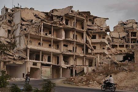 Motorradfahrer passieren zerstörte Gebäude in der Provinz Idlib. Das Auswärtige Amt schätzt nicht nur die Region um Idlib, sondern ganz Syrien als gefährlich für Rückkehrer ein. Foto: Ugur Can/DHA via AP/dpa