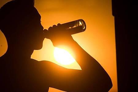 Ein junger Mann sitzt auf dem Kronsberg, und trinkt Bier, während am Horizont die Sonne untergeht. Foto: Julian Stratenschulte/dpa