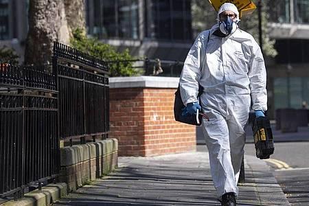Ein Mann geht im Schutzanzug über eine Straße in Westminster im Zentrum Londons. Foto: Victoria Jones/PA Wire/dpa