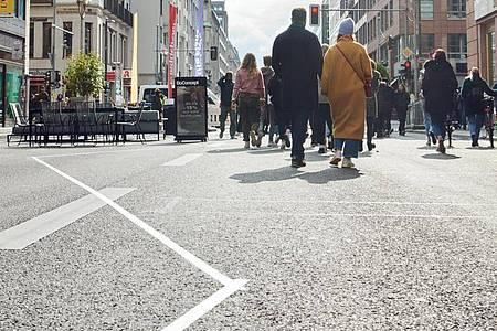 Menschen flanieren mitten auf der Friedrichstraße. Das Modellprojekt zur autofreien Friedrichstraße in Berlin wird jetzt in die Tat umgesetzt. Foto: Annette Riedl/dpa