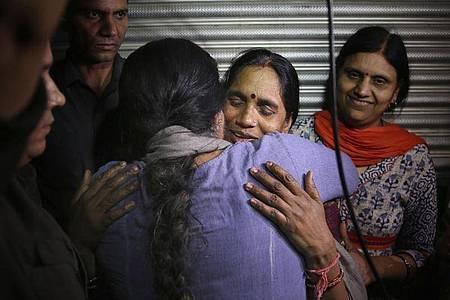 Asha Devi, die Mutter des Opfers, wird umarmt, nachdem die Vergewaltiger ihrer Tochter hingerichtet worden sind. Foto: Altaf Qadri/AP/dpa