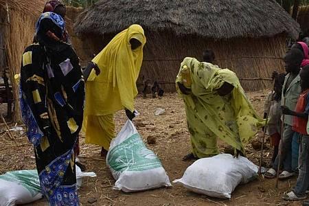 Drei Frauen nehmen im Sudan Spenden einer humanitären Organisation entgegen. Bei einer Online-Geberkonferenz kamen rund 1,8 Milliarden Dollar für den Reformprozess im Sudan zusammen. Foto: -/Saudi Press Agency/dpa