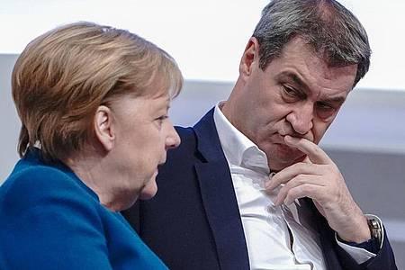 Bundeskanzlerin Merkel spricht mit Markus Söder 2019 beim 32. CDU-Bundesparteitag. Foto: Michael Kappeler/dpa