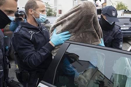 Beamte des Zoll führen den in Frankfurt festgenommenen Hauptbeschuldigten mit einer Decke über dem Kopf ab. Bei dem in Frankfurt festgenommenen Mann handelt es sich um einen Mann aus dem Umfeld der Hells-Angels. Foto: Boris Roessler/dpa