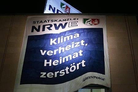 Greenpeace Aktivisten haben am Düsseldorfer Staatskanzlei zwei Banner aufgespannt. Auf dem Banner steht «Staatskanzlei NRWE: Klima verheizt, Heimat zerstört». Foto: David Young/dpa
