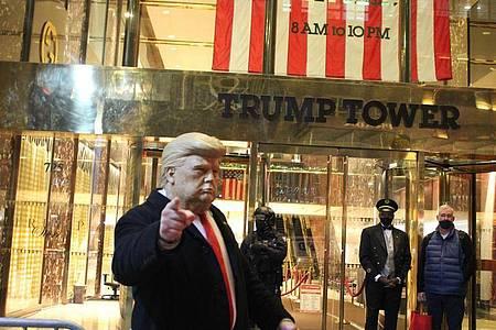 Ein Mann mit einer Trump-Maske in der Hand gestikuliert vor dem Trump Tower, der von einem Polizisten einer Spezialeinheit des NYPD auf der 5th Avenue in Manhattan am Vorabend der Präsidentschaftswahlen gesichert wird. Foto: Marie Le Ble/ZUMA Wire/dpa