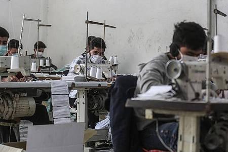Arbeiter in der umkämpften Region Idlib mit Gesichtsmasken. In einem kleinen Labor stellen sie notdürftig Schutzmasken her. Foto: Anas Alkharboutli/dpa