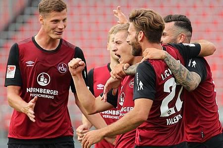 Der Nürnberger Fabian Nürnberger (M) jubelt mit seinen Kollegen Patrick Erras (l), Mikael Ishak (r) und Enrico Valentini über seinen Treffer zum 2:0. Foto: Daniel Karmann/dpa
