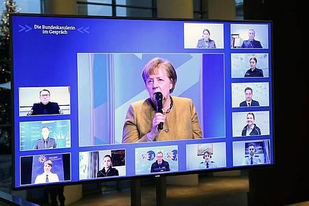 Kanzlerin Angela Merkel spricht mit Polizeibeamten und Polizeibeamtinnen. Foto: Annegret Hilse/Reuters Images Europe/Pool/dpa