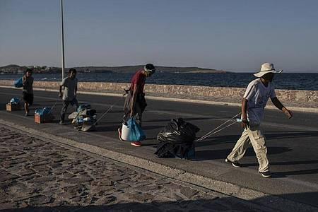 Flüchtlinge auf Lesbos ziehen ihre Habseligkeiten hinter sich her. Foto: Petros Giannakouris/AP/dpa