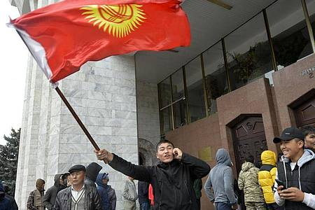 Demonstranten stehen vor dem Regierungsgebäude in Bischtek. Unter dem Druck massiver Proteste hatte die Wahlleitung im zentralasiatischen Kirgistan die Parlamentswahl für ungültig erklärt. Foto: Vladimir Voronin/AP/dpa