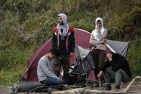 Migranten ruhen vor einem Zelt im Dorf Petra auf der nordöstlichen Ägäisinsel Lesbos in Griechenland. Foto: Panagiotis Balaskas/AP/dpa