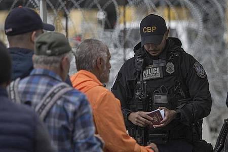 Ein Grenzbeamter kontrolliert in Tijuana am Grenzübergang zwischen Mexiko und den USA einen Pass. Foto: Omar Martínez/dpa