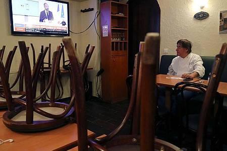 Ein Restaurantbesitzer schaut sich in Paris auf einem Nachrichtensender eine Fernsehansprache des französischen Premierministers Philippe an. Foto: Ludovic Marin/AFP/dpa