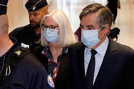 Francois Fillon (r), ehemaliger Premierminister von Frankreich, und seine Frau Penelope Fillon (2.v.r) beim Verlassen des Gerichtsgebäudes. Foto: Thomas Samson/AFP/dpa