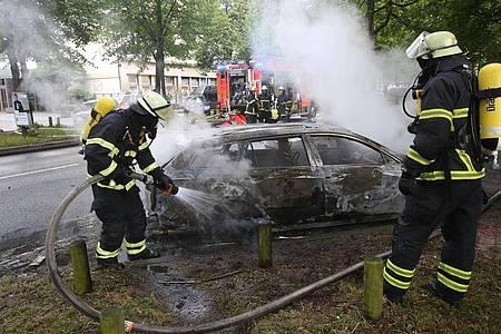 Feuerwehrleute löschen während des G20-Gipfels im Jahr 2017 ein brennendes Auto in Hamburg-Altona. Foto: Bodo Marks/dpa