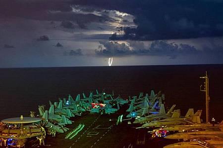 Militärjets stehen auf dem Flugdeck des Flugzeugträgers USS Nimitz (CVN 68) im Südchinesischen Meer während eines Gewitters. Die «USS Nimitz» und die «USS Ronald Reagan» führen als Nimitz Carrier Strike Force Dual Carrier-Operationen im Südchinesischen Meer ein Manöver durch. Foto: John Wagner/Navy Office of Information/dpa
