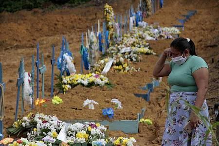 Eine Frau trauert an einem Grab auf einem Friedhof in Manaus. Foto: Altemar Alcantara/Semcom/Bürgermeisteramt Manaus/dpa