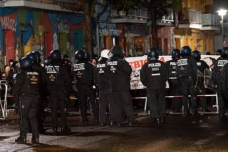 Polizisten stehen vor Demonstranten, die gegen die Räumung des besetzten Hauses «Liebig 34» protestieren. Foto: Paul Zinken/dpa