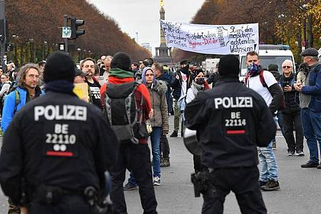 Teilnehmer einer Demonstration gegen die Corona-Einschränkungen der Bundesregierung potestieren nahe dem Brandenburger Tor. Foto: Paul Zinken/dpa