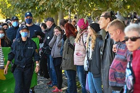 Menschen bilden eine sogenannte Friedensmenschenkette, die durch Deutschland, Österreich, Liechtenstein und die Schweiz rund um den Bodensee führen soll. Foto: Felix Kästle/dpa