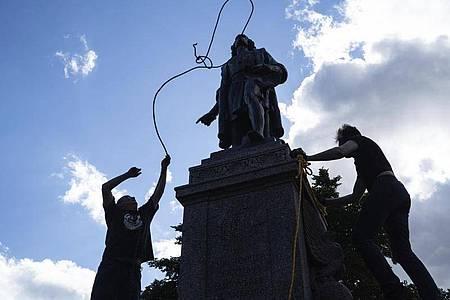 Zwei Männer befestigen ein Seil um den Hals einer Statue von Christopher Columbus. Foto: Evan Frost/Minnesota Public Radio/AP/dpa