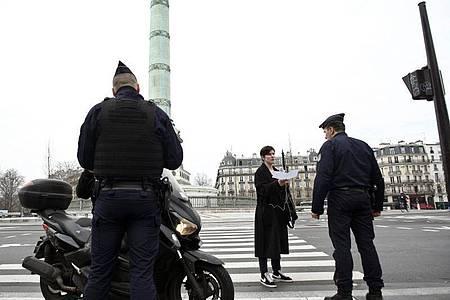 Polizeibeamte kontrollieren die Ausgangsformulare an einer Kontrollstelle in Paris. Foto: Thibault Camus/AP/dpa