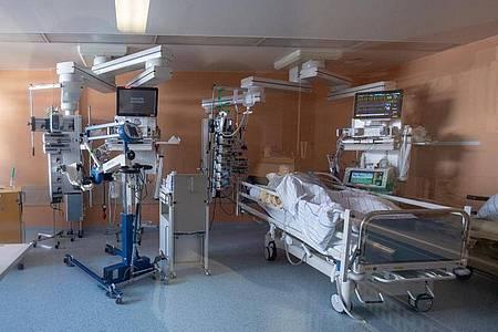 Ein positiv getesteter Corona-Patient in einem isoliertem Intensivbett-Zimmer. Foto: Peter Kneffel/dpa