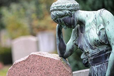 Eine Frauenfigur lehnt an einem Grabstein. Foto: picture alliance / dpa