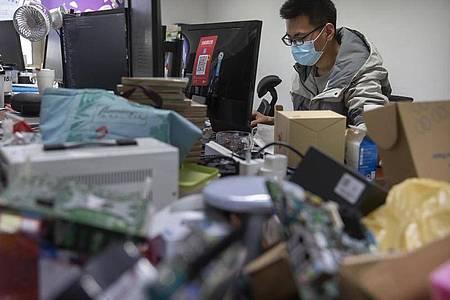 Ein Mann trägt bei der Arbeit in einem Technologieunternehmen in Peking einen Mundschutz. Foto: Mark Schiefelbein/AP/dpa