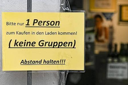 Ein Schild regelt den Einlass in ein Geschäft in Hamburg. Foto: Axel Heimken/dpa