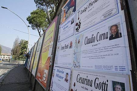 Todesanzeigen auf einer Tafel am Rand einer leeren Straße in Alzano Lombardo unweit von Bergamo. Foto: Luca Bruno/AP/dpa