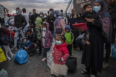 Flüchtlinge aus dem Lager Moria auf Lesbos gehen im Hafen von Piräus bei Athen an Land. Die Asylreform kommt seit Jahren kaum voran, weil die EU-Staaten vor allem bei der Verteilung von Schutzsuchenden völlig zerstritten sind. Foto: Angelos Tzortzinis/dpa/dpa