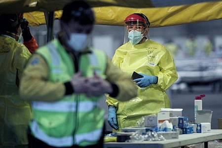Gesundheitspersonal mit Schutzkleidung arbeitet auf der Madrider Messe, wo Patienten mit leichten Symptomen des Coronavirus behandelt werden. Foto: Eduardo Parra/Europa Press/dpa