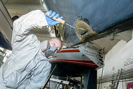 Überkopf-Arbeiten beim Bootsbau sind anstrengend: Auszubildende Carina Isenberg laminiert eine Schadstelle am Rumpf mit Glasfasermatten und Kunstharz. Foto: Markus Scholz/dpa-tmn