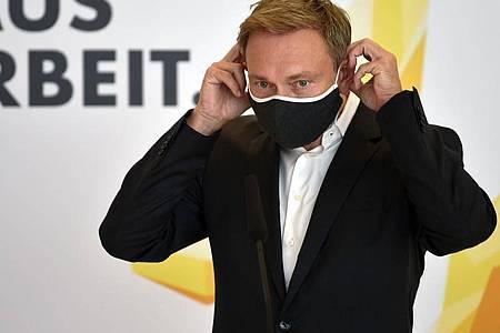 Christian Lindner, Bundesvorsitzender der FDP, legt einen Mund-Nasen-Schutz auf einer Pressekonferenz an. Die Bundestagsfraktion der FDP traf sich zu ihrer Klausurtagung im Reichstagsgebäude. Foto: Johannes Neudecker/dpa