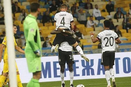 Matthias Ginter, Torschütze zum 1:0, wird von Mannschaftskamerad Antonio Rüdiger beim jubeln hochgehoben - Serge Gnabry kommt zum feiern dazu. Foto: Efrem Lukatsky/AP/dpa