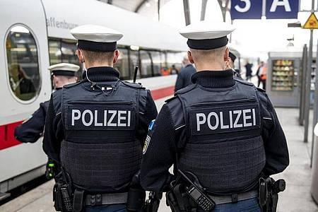 Bundespolizisten stehen vor der Abfahrt eines ICE an einem Gleis im Kieler Hauptbahnhof. In den Zügen der Deutschen Bahn wird die Mund-Nase-Bedeckungspflicht kontrolliert. Foto: Axel Heimken/dpa