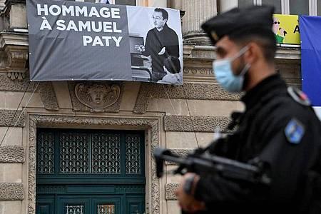 Ein Polizist steht neben der Opera Comedie in Montpellier, an deren Fassade eine Hommage an den enthaupteten Lehrer Samuel Paty angebracht ist. Foto: Pascal Guyot/AFP/dpa