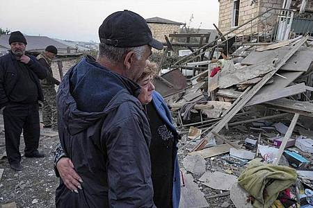 Ein Paar steht vor den Trümmern eines zerstörten Hauses in Berg-Karabach. Foto: Uncredited/AP/dpa
