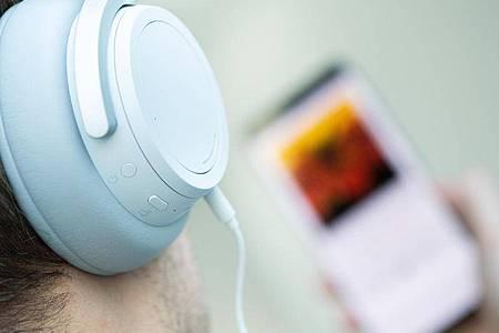 Ein junger Mann hört auf seinem Smartphone einen Podcast. Foto: Franziska Gabbert/dpa-tmn/dpa