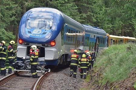 Rettungskräfte inspizieren am Unglücksort die Züge, die miteinander kollidiert sind. Foto: Slavomír Kubeš/CTK/dpa