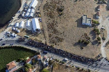 Eine größere Gruppe von Migranten wartet darauf, in das neue provisorische Flüchtlingslager gelassen zu werden. Foto: Petros Giannakouris/AP/dpa