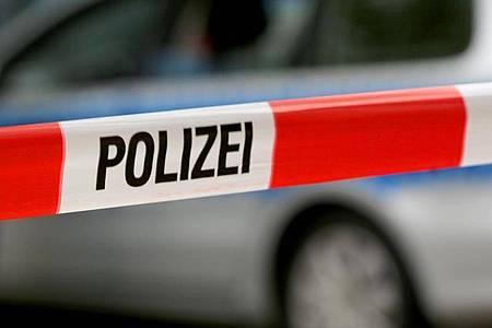 Ein Einsatzfahrzeug der Polizei hinter einer Polizeiabsperrung. Foto: Oliver Berg/dpa/Symbolbild