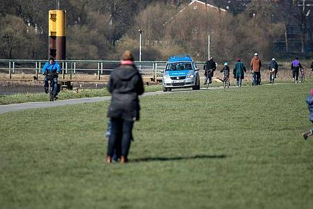Polizei fährt den Osterdeich in Bremen entlang, um das Kontaktverbot zu kontrollieren. Foto: Sina Schuldt/dpa