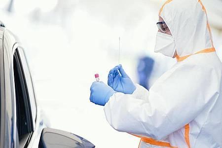 Medizinisches Personal in Schutzkleidung nimmt in einem mobilen Corona-Abstrichzentrum in Baden-Württemberg einen Abstrich. Foto: Uwe Anspach/dpa